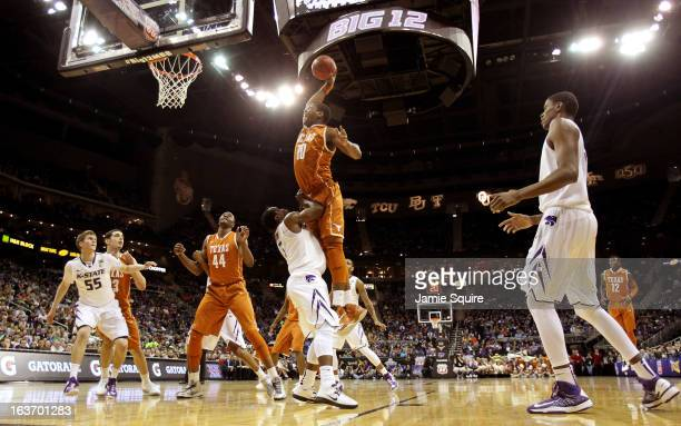 Jonathan Holmes of the Texas Longhorns drives to the basket against Martavious Irving of the Kansas State Wildcats in the first half during the...