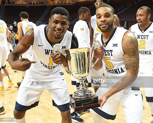 Jonathan Holton and Jaysean Paige of the West Virginia Mountaineers celebrate with the championship trophy after defeating the San Diego State Aztecs...