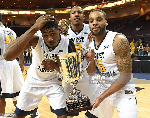 Jonathan Holton Jevon Carter and Jaysean Paige of the West Virginia Mountaineers celebrate with the championship trophy after defeating the San Diego...