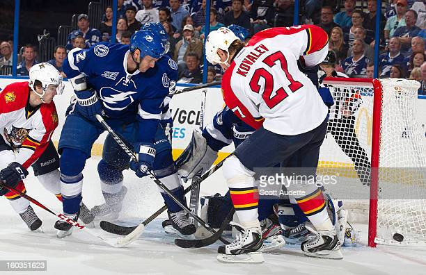 Jonathan Huberdeau and Alex Kovalev of the Florida Panthers look for a rebound in front of goaltender Anders Lindback and Eric Brewer of the Tampa...