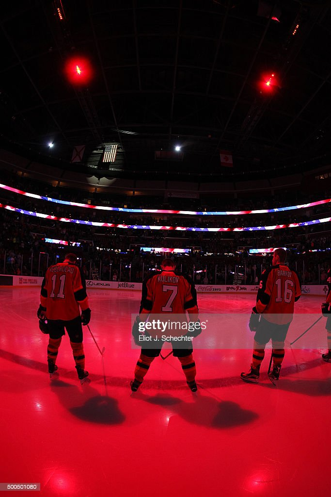 Jonathan Huberdeau #11 of the Florida Panthers and teammates Dmitry Kulikov #7 and Aleksander Barkov #16 stand on the ice for the national anthems prior to the start of the game against the Ottawa Senators at the BB&T Center on December 8, 2015 in Sunrise, Florida.