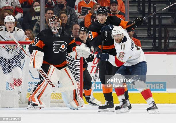 Jonathan Huberdeau of the Florida Panthers battles for position with Oskar Lindblom of the Philadelphia Flyers in front of goaltender Carter Hart at...