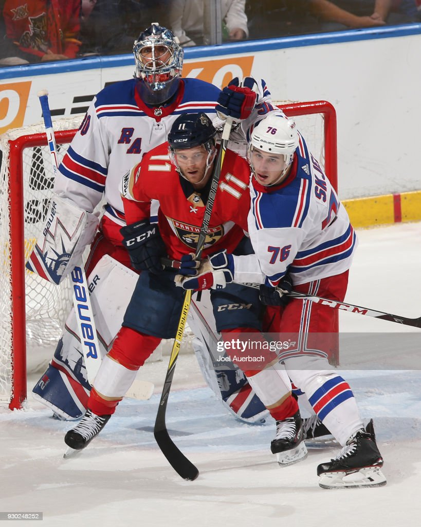 Jonathan Huberdeau #11 of the Florida Panthers battles for position with Brady Skjei #76 in front of goaltender Henrik Lundqvist #30 of the New York Rangers at the BB&T Center on March 10, 2018 in Sunrise, Florida. The Panthers defeated the Rangers 4-3 in a shootout.