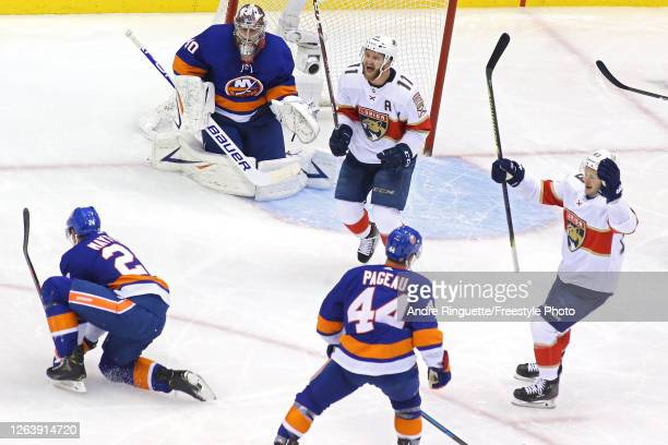 Jonathan Huberdeau of the Florida Panthers celebrates in front of goalie Semyon Varlamov of the New York Islanders after teammate Aleksander Barkov...