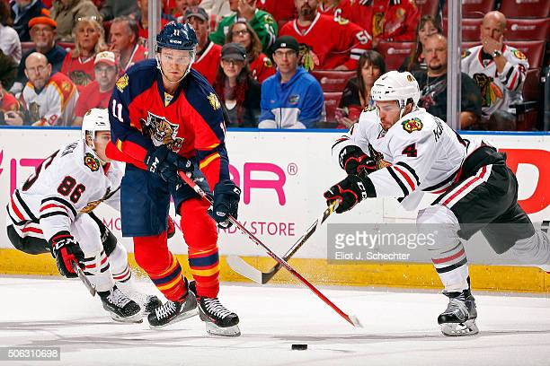 Jonathan Huberdeau of the Florida Panthers crosses sticks with Niklas Hjalmarsson of the Chicago Blackhawks during the first period at the BBT Center...