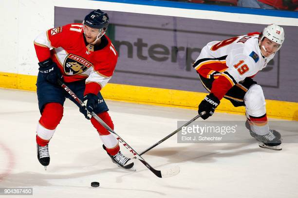 Jonathan Huberdeau of the Florida Panthers crosses sticks with Matthew Tkachuk of the Calgary Flames at the BBT Center on January 12 2018 in Sunrise...