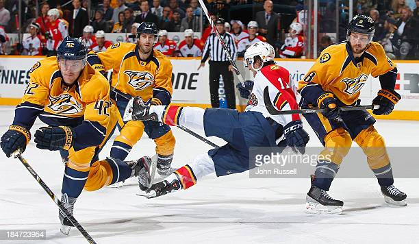 Jonathan Huberdeau of the Florida Panthers is upended by Mattias Ekholm and Kevin Klein of the Nashville Predators at Bridgestone Arena on October 15...