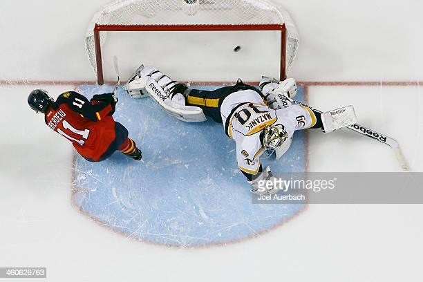 Jonathan Huberdeau of the Florida Panthers scores a shootout goal past goaltender Marek Mazanec of the Nashville Predators at the BBT Center on...