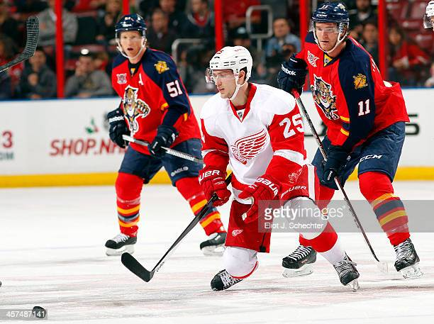 Jonathan Huberdeau of the Florida Panthers skates for possession against Cory Emmerton of the Detroit Red Wings at the BBT Center on December 10 2013...