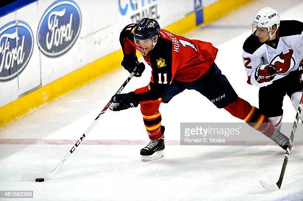 Jonathan Huberdeau of the Florida Panthers skates with the puck as Damien Brunner of the New Jersey Devils chases at the BBT Center on March 14 2014...