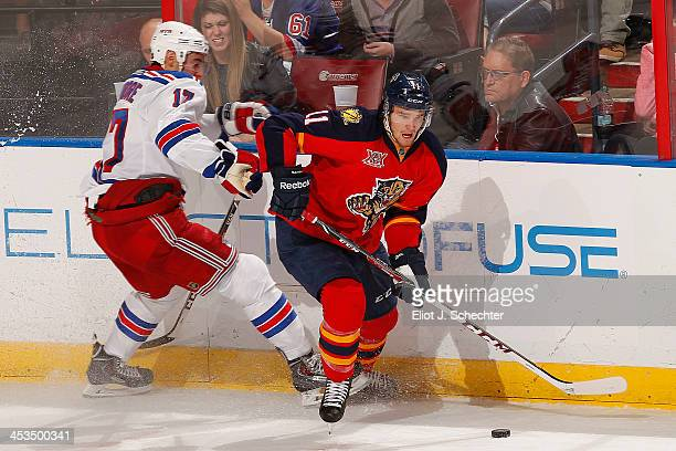 Jonathan Huberdeau of the Florida Panthers skates with the puck against John Moore of the New York Rangers at the BBT Center on November 27 2013 in...