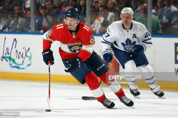 Jonathan Huberdeau of the Florida Panthers skates with the puck against Leo Komarov of the Toronto Maple Leafs at the BBT Center on March 14 2017 in...