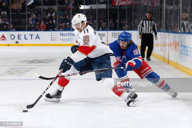 Jonathan Huberdeau of the Florida Panthers skates with the puck against Artemi Panarin of the New York Rangers at Madison Square Garden on November...