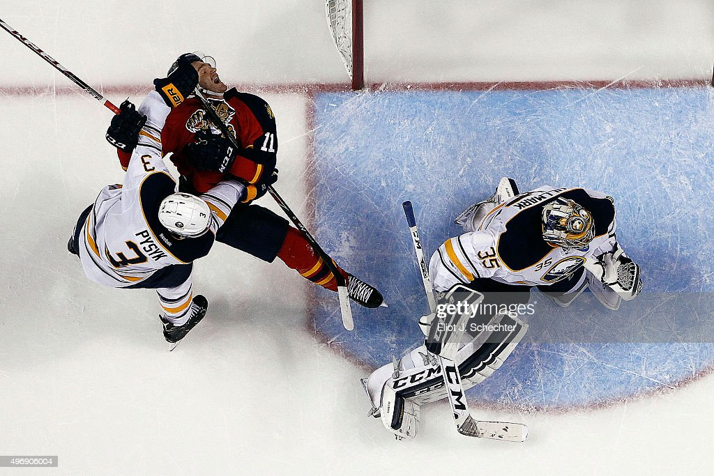 Jonathan Huberdeau #11 of the Florida Panthers tangles with Mark Pysyk #3 of the Buffalo Sabres while teammate Goaltender Linus Ullmark #34 defends the net at the BB&T Center on November 12, 2015 in Sunrise, Florida.