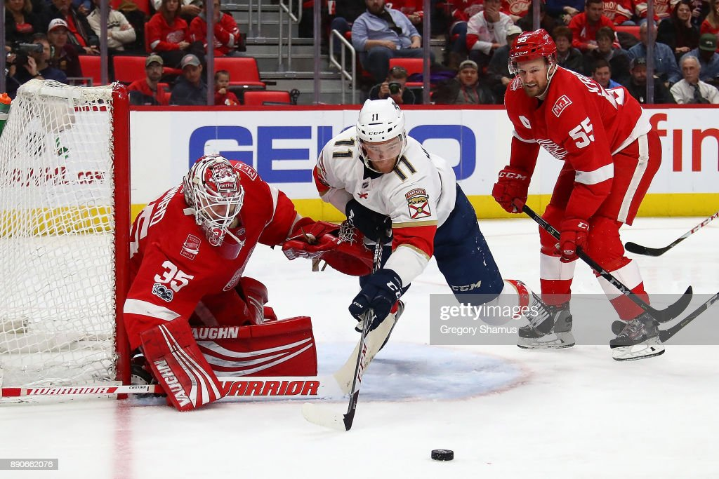 Jonathan Huberdeau #11 of the Florida Panthers tries to get to the puck next to Jimmy Howard #35 of the Detroit Red Wings at Little Caesars Arena on December 11, 2017 in Detroit, Michigan. Florida won the game 2-1 in overtime.