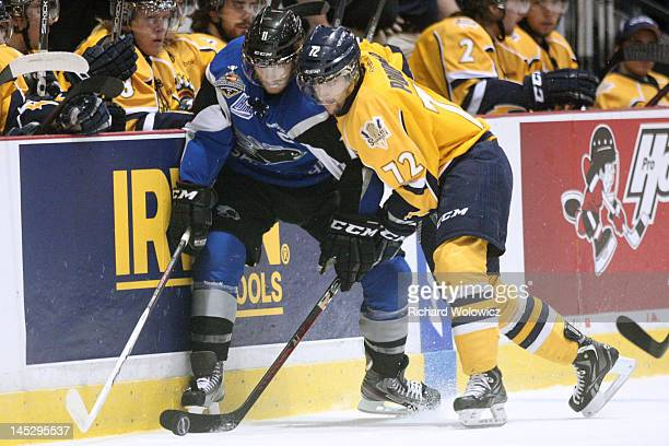 Jonathan Huberdeau of the Saint John Sea Dogs and Loïk Poudrier of the Shawinigan Cataractes battle for the puck along the boards during the 2012...