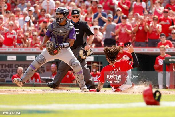 Jonathan India of the Cincinnati Reds slides past Elias Diaz of the Colorado Rockies to score a run during the first inning of the game at Great...