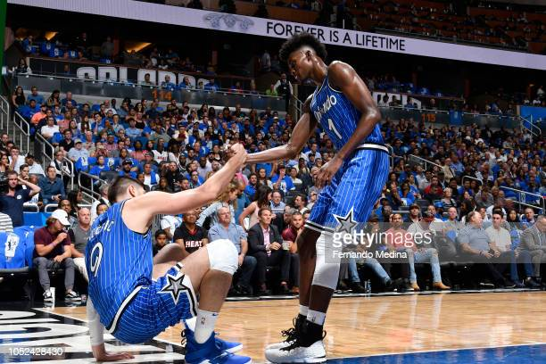 Jonathan Isaac helps up Nikola Vucevic of the Orlando Magic during the game against the Miami Heat on October 17 2018 at Amway Center in Orlando...