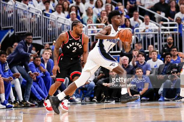 Jonathan Isaac of the Orlando Magic passes the ball off as he is defended by Kawhi Leonard of the Toronto Raptors during Game Three of the first...