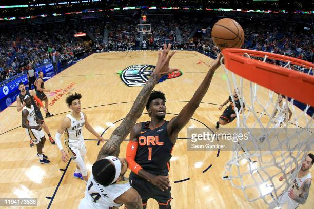 Jonathan Isaac of the Orlando Magic shoots over Brandon Ingram of the New Orleans Pelicans during a NBA game at Smoothie King Center on December 15,...