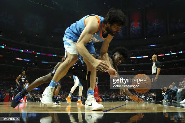 Jonathan Isaac of the Orlando Magic vies for the ball with Milos Teodosic of the Los Angeles Clippers during the first half of the NBA game between...