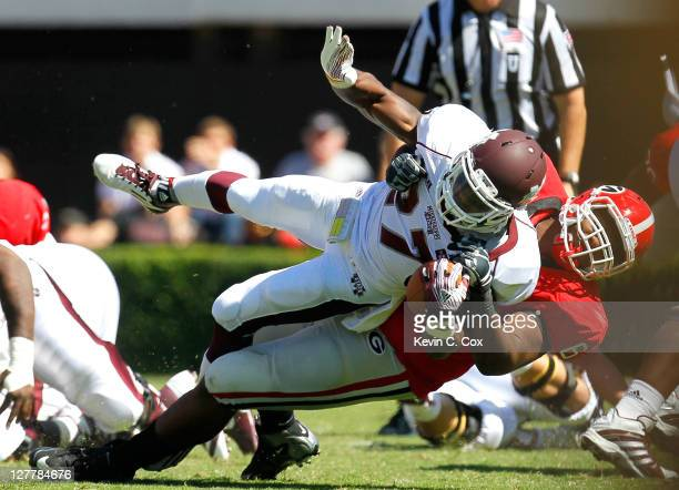 Jonathan Jenkins of the Georgia Bulldogs picks up and tackles LaDarius Perkins of the Mississippi State Bulldogs at Sanford Stadium on October 1,...