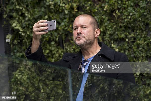 Jonathan Jony Ive chief design officer for Apple Inc uses an Apple iPhone to take a photograph of the plaza area during the grand opening of the...