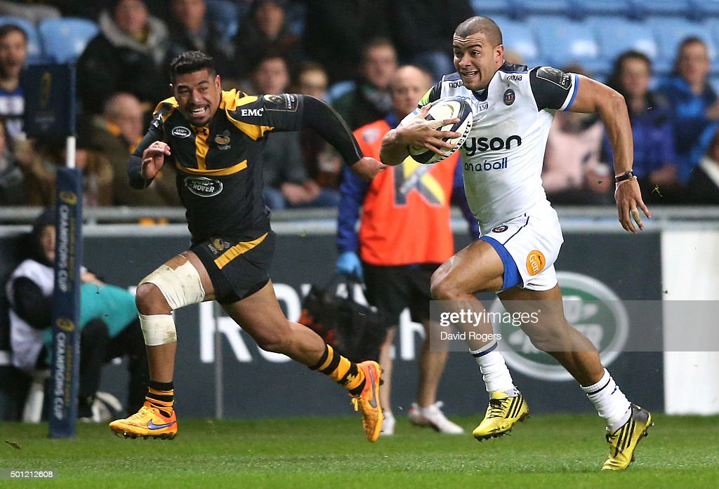 Jonathan Joseph of Bath breaks away from Charles Piutau for the first try during the European Rugby Champions Cup match between Wasps and Bath at the Ricoh Arena on December 13, 2015 in Coventry, England.