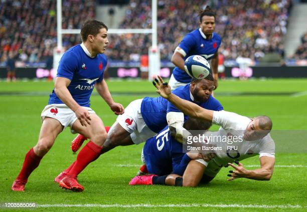 Jonathan Joseph of England is tackled by Anthony Bouthier and Virimi Vakatawa of France during the 2020 Guinness Six Nations match between France and...