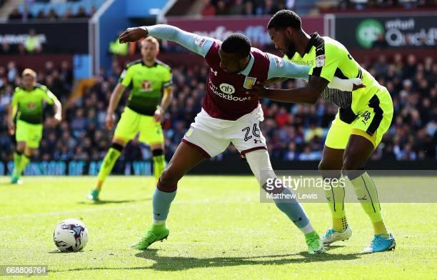 Jonathan Kodjia of Aston Villa holds off Tyler Blackett of Reading during the Sky Bet Championship match between Aston Villa and Reading at Villa...