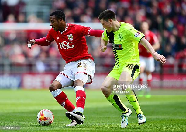 Jonathan Kodjia of Bristol City holds off Joe Lolley of Huddersfield Town during the Sky Bet Championship match between Bristol City and Huddersfield...