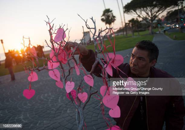 Jonathan Kostka of Rancho Santa Margarita hangs the name of his friend Martine Salas on a memorial during the World AIDS Day Remembrance at Main...