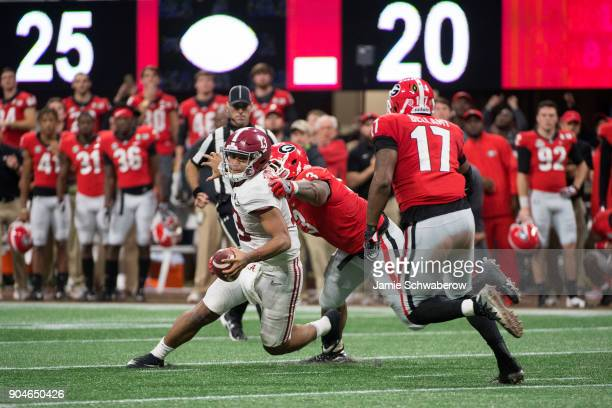 Jonathan Ledbetter and Davin Bellamy of the Georgia Bulldogs sack Tua Tagovailoa of the Alabama Crimson Tide on the second to last play of the game...