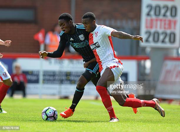 Jonathan Leko of West Bromwich Albion is tackled by Tyrone Williams of Kidderminster Harriers during the PreSeason Friendly match between...