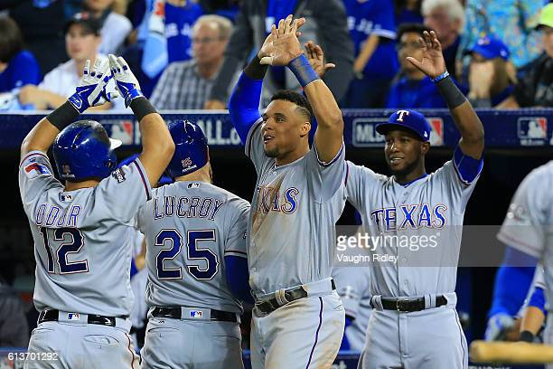 Jonathan Lucroy and Rougned Odor of the Texas Rangers celebrate with teammates after scoring on a two run double hit by Mitch Moreland in the sixth...