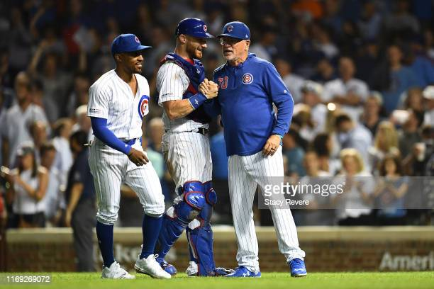 Jonathan Lucroy of the Chicago Cubs is congratulated by manager Joe Maddon following a victory over the San Francisco Giants at Wrigley Field on...