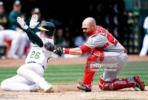 Jonathan Lucroy of the Los Angeles Angels of Anaheim tags out Matt Chapman of the Oakland Athletics at home plate in the bottom of the third inning...