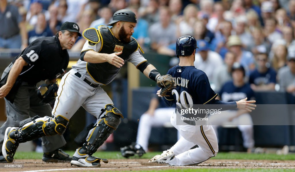 Jonathan Lucroy #20 of the Milwaukee Brewers beats the tag from Russell Martin #55 of the Pittsburgh Pirates at home plate putting the\e Brewers up 4-2 in the bottom of the send inning during the game at Miller Park on August 24, 2014 in Milwaukee, Wisconsin.