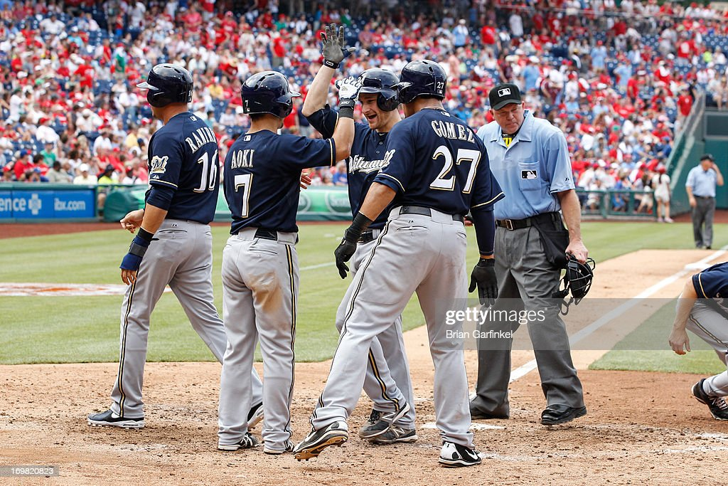 Jonathan Lucroy #20 of the Milwaukee Brewers is congratulated by teammates at home plate in the eighth inning of the game against the Philadelphia Phillies at Citizens Bank Park on June 2, 2013 in Philadelphia, Pennsylvania. The play was originally called as a Grand slam but after review it was called as a three run triple. The Phillies won 7-5.