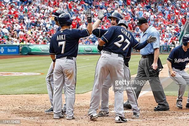 Jonathan Lucroy of the Milwaukee Brewers is congratulated by teammates at home plate in the eighth inning of the game against the Philadelphia...