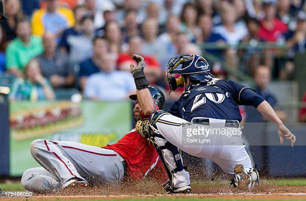 Jonathan Lucroy of the Milwaukee Brewers is late with the tag on Jayson Werth of the Washington Nationals in the second inning at Miller Park on...