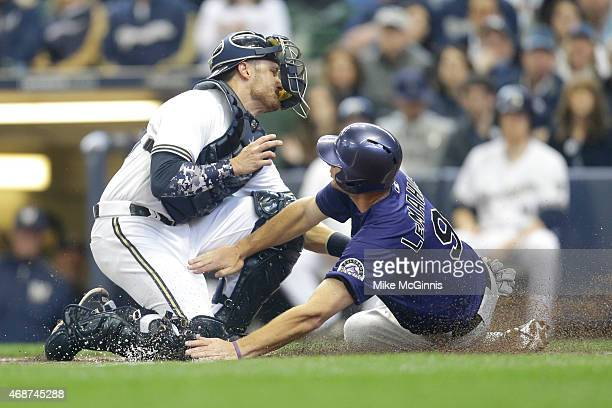Jonathan Lucroy of the Milwaukee Brewers makes the tag on DJ LaMahieu of the Colorado Rockies as he slides into home plate during the second inning...