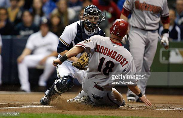 Jonathan Lucroy of the Milwaukee Brewers tags out Willie Bloomquist of the Arizona Diamondbacks at home plate during Game One of the National League...