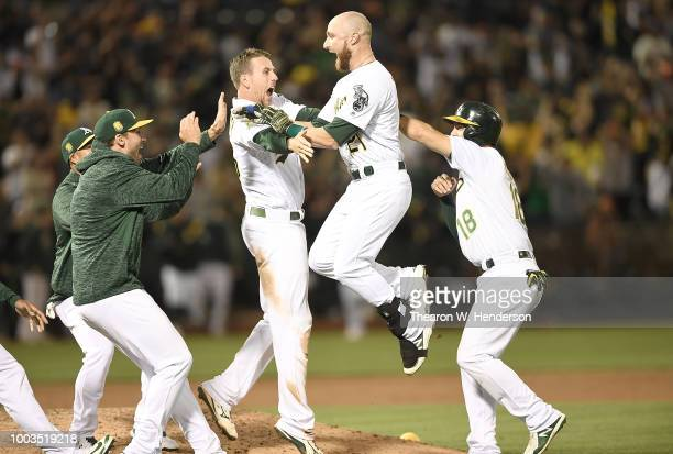 Jonathan Lucroy of the Oakland Athletics celebrates with teammates after he hit an rbi walk off single to defeat the San Francisco Giants 43 in the...