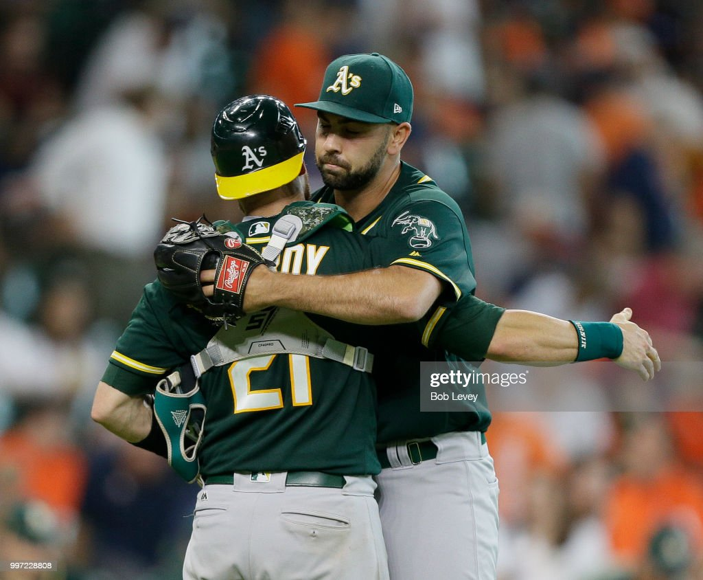 Jonathan Lucroy #21 of the Oakland Athletics hugs Lou Trivino #62 afetr the final out against the Houston Astros at Minute Maid Park on July 12, 2018 in Houston, Texas. Oakland won 6-4.