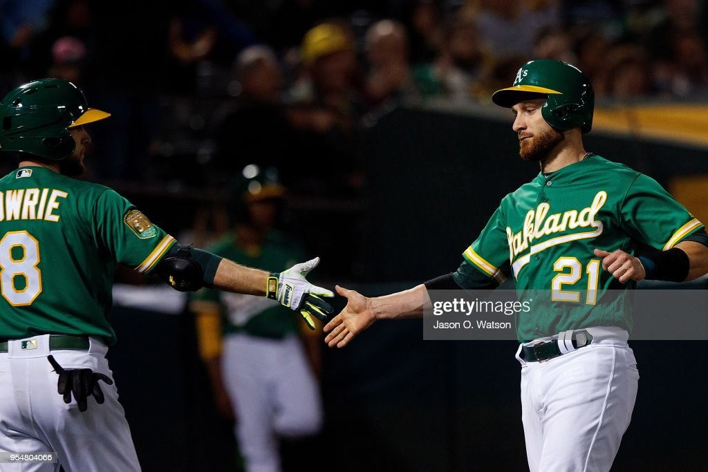 Jonathan Lucroy #21 of the Oakland Athletics is congratulated by Jed Lowrie #8 after scoring a run against the Baltimore Orioles during the eighth inning at the Oakland Coliseum on May 4, 2018 in Oakland, California. The Oakland Athletics defeated the Baltimore Orioles 6-4.