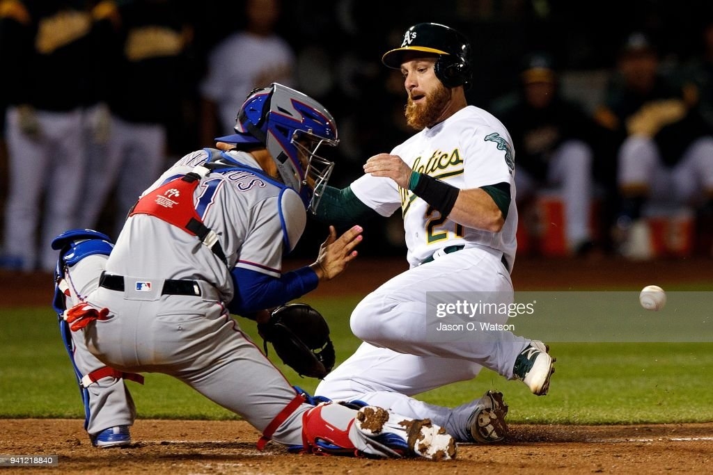 Jonathan Lucroy #21 of the Oakland Athletics is tagged out at home plate by Robinson Chirinos #61 of the Texas Rangers during the fifth inning at the Oakland Coliseum on April 2, 2018 in Oakland, California. The Oakland Athletics defeated the Texas Rangers 3-1.