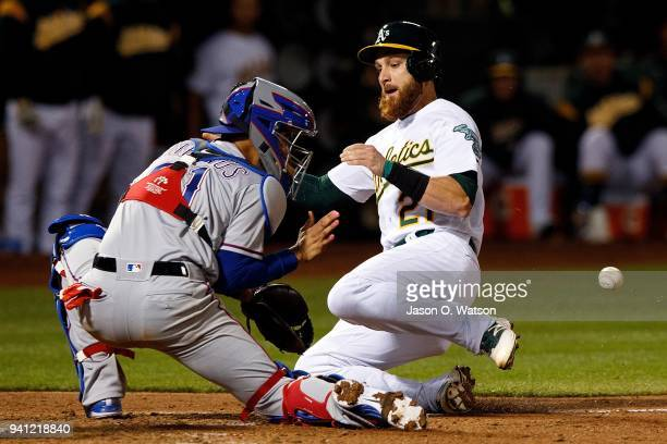 Jonathan Lucroy of the Oakland Athletics is tagged out at home plate by Robinson Chirinos of the Texas Rangers during the fifth inning at the Oakland...