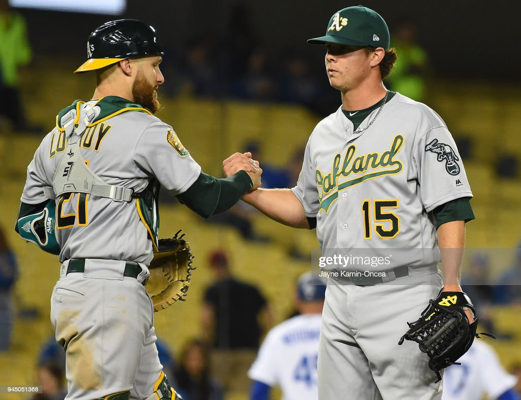 Jonathan Lucroy #21 of the Oakland Athletics shakes hands with Emilio Pagan #15 of the Oakland Athletics who earned a save in the game against the Los Angeles Dodgers at Dodger Stadium on April 11, 2018 in Los Angeles, California.