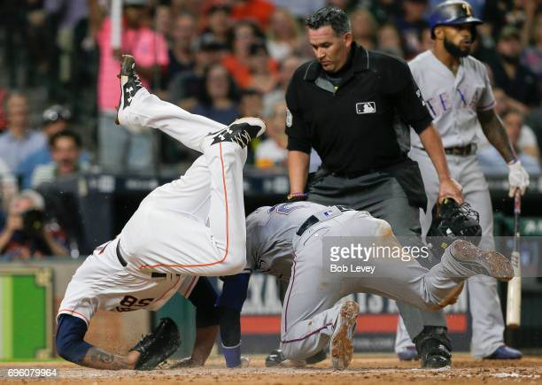 Jonathan Lucroy of the Texas Rangers scores on a wild pitch in the fifth inning asFrancis Martes of the Houston Astros tumbles over him at Minute...